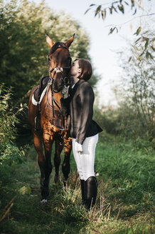 Side view of female rider kissing horse while standing on grassy field - CAVF61683