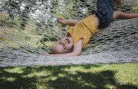 Portrait of happy girl lying on hammock against grassy field at yard - CAVF61719