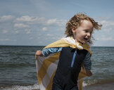 Happy girl wearing cape while running by sea against sky during sunny day - CAVF61725