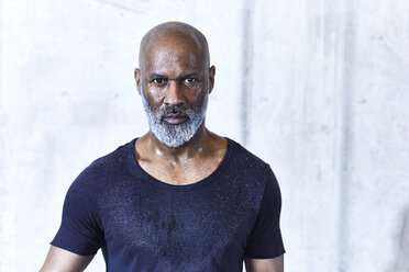 Portrait of sweating bald man with grey beard wearing dark blue jersey - FMKF05420