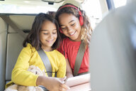Sisters using digital tablet in back set of car - CAIF22801