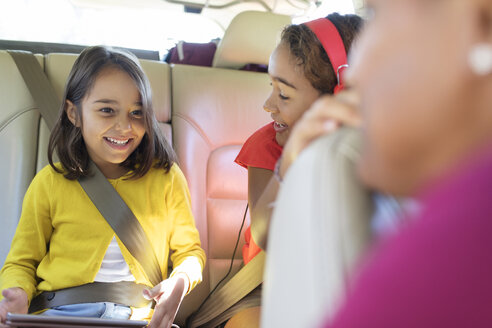 Happy sisters riding in back seat of car with digital tablet - CAIF22816