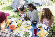 Family enjoying lunch at campsite table - CAIF22837