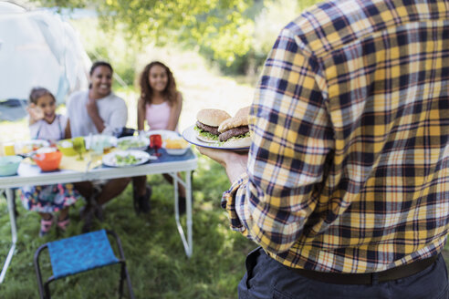 Father serving barbecue hamburgers to family at campsite table - CAIF22840