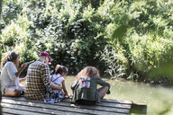 Family relaxing on dock in woods - CAIF22843