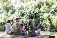 Family blowing bubbles on dock in woods - CAIF22846