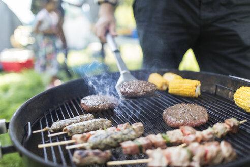 Man barbecuing hamburgers, kebabs and corn cobs - CAIF22849