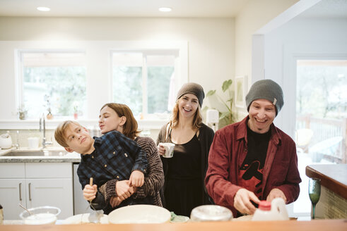 Portrait happy, playful family baking in kitchen - CAIF22870
