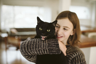 Portrait girl holding hissing black cat - CAIF22882