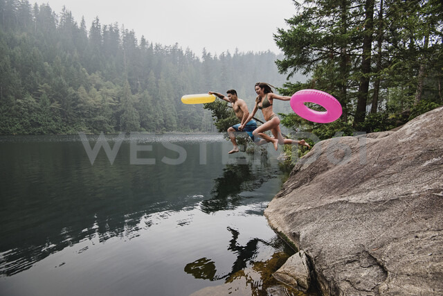 Playful young couple with inflatable rings jumping into remote lake, Squamish, British Columbia, Canada - CAIF22885 - Jarusha Brown/Westend61