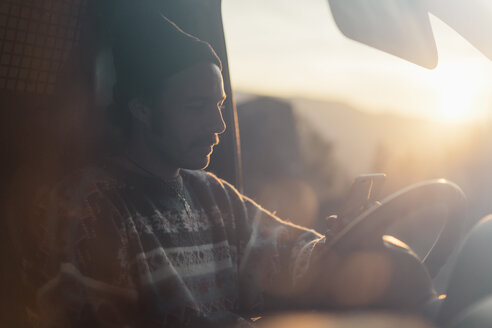 Young man on a road trip, using smartphone - AFVF02498