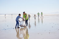Mother and son volunteers cleaning litter on sunny, wet sand beach - CAIF22903