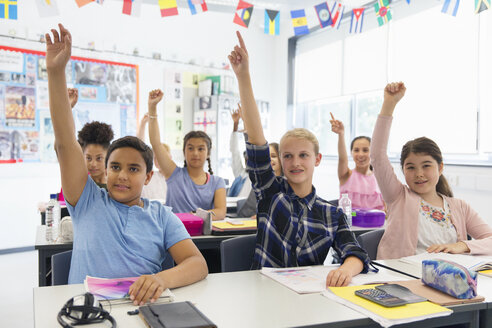 Eager junior high school students with hands raised in classroom - CAIF22912