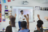 Smiling male teacher leading lesson in classroom - CAIF22918