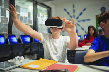 Curious junior high school boy student using virtual reality simulator in classroom - CAIF22921