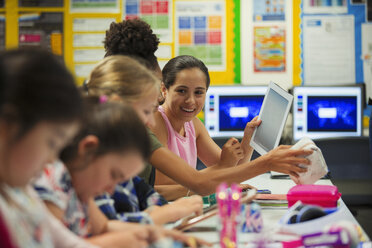 Junior high school girl students using digital tablet in classroom - CAIF22942