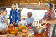 Friends enjoying healthy meal in hut during yoga retreat - CAIF22948
