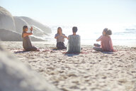 Group meditating in circle on sunny beach during yoga retreat - CAIF22963