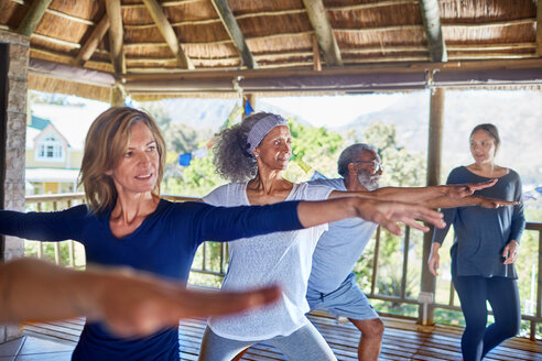 Yoga class practicing warrior 2 pose in hut during yoga retreat - CAIF22990