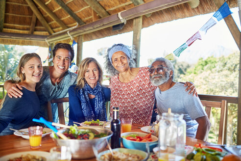 Portrait happy friends enjoying healthy meal in hut during yoga retreat - CAIF22996