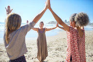 Women joining hands in circle on sunny beach during yoga retreat - CAIF23008