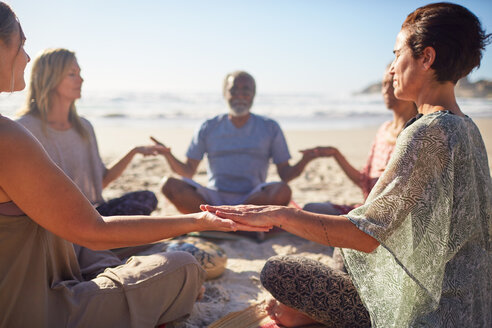Serene people meditating in circle on sunny beach during yoga retreat - CAIF23011
