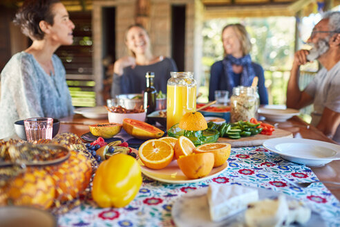 Friends enjoying healthy breakfast at table during yoga retreat - CAIF23017