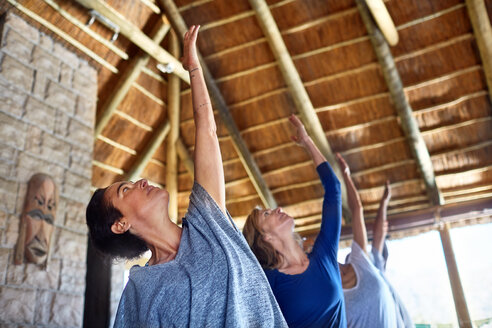 Women practicing yoga during retreat in hut - CAIF23020