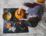 High angle view of boy removing seeds from pumpkin at home - CAVF61765