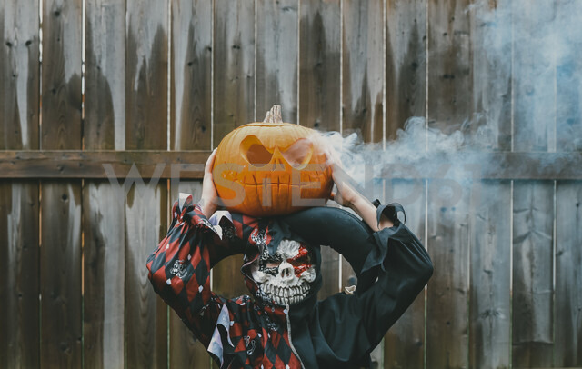 Boy dressed in costume holding jack o' lantern while standing against fence in backyard - CAVF61768 - Cavan Images/Westend61