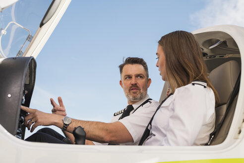 Low angle view of male pilot teaching trainee to operate control panel in airplane against blue sky at airport - CAVF61798
