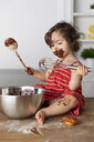 Cute baby girl eating chocolate while sitting with kitchen utensils on wooden table against wall at home - CAVF61816