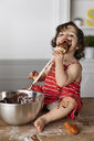 Baby girl eating chocolate while sitting on wooden table against wall at home - CAVF61819