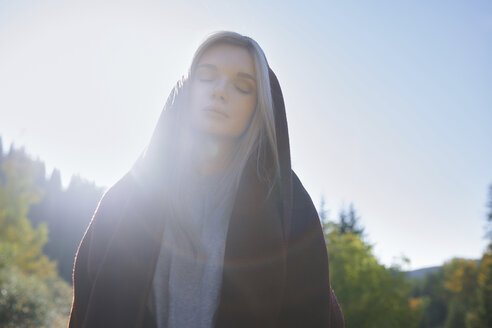 Portrait of young woman with hood at backlight - AZF00129