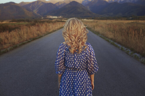 USA, California, back view of strawberry blonde woman on country road - AZF00132