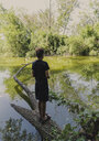 Full length of boy fishing while standing on fallen tree in lake at forest - CAVF61846