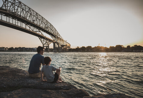 Father and son looking at view while sitting on rocks by sea against sky during sunset - CAVF61849