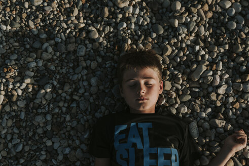 Overhead view of boy with eyes closed lying on pebbles at beach during sunset - CAVF61855