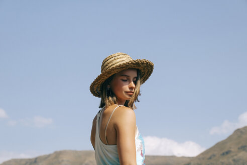 Side view of woman with eyes closed wearing hat while standing against blue sky during sunny day - CAVF61885