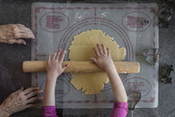 Cropped hands of granddaughter rolling cookie dough by grandmother on table at home - CAVF61903