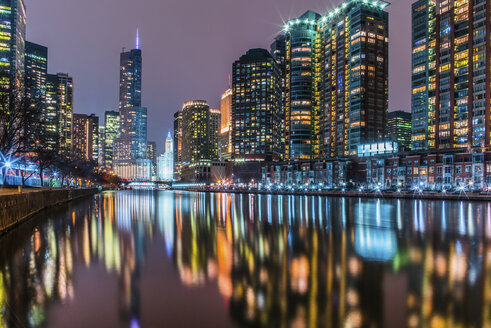 Illuminated modern buildings reflecting on calm Chicago River against sky at night - CAVF61987