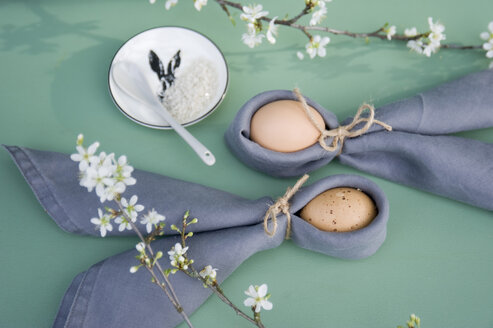 Easter decoration, Twigs of sloe, napkins with Easter eggs, folded as rabbit ears - GISF00397