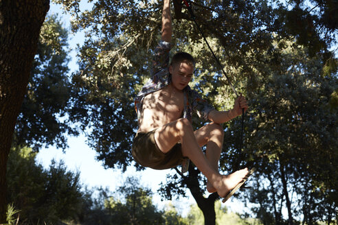 France, teenage boy on a swing at tree - AMEF00007