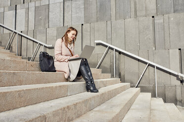 Austria, Vienna, smiling young woman sitting on stairs at MuseumsQuartier using laptop - ZEDF01932