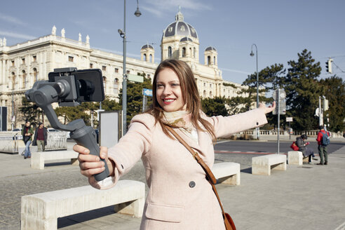 Austria, Vienna, portrait of smiling young woman using selfie-stick for taking photo with smartphone - ZEDF01941