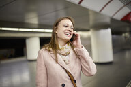 Austria, Vienna, portrait of smiling young woman on the phone at underground station platform - ZEDF01944