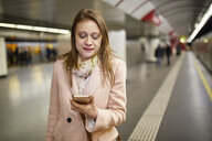 Austria, Vienna, portrait of smiling young woman looking at smartphone at underground station platform - ZEDF01947