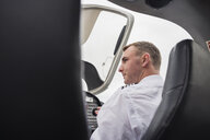 Rear view of serious male pilot looking away while sitting in airplane against sky at airport - CAVF62039