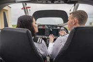 Rear view of male pilot giving training to female trainee while sitting in airplane at airport - CAVF62042