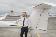 Portrait of confident male pilot standing by airplane on airport runway against cloudy sky - CAVF62051